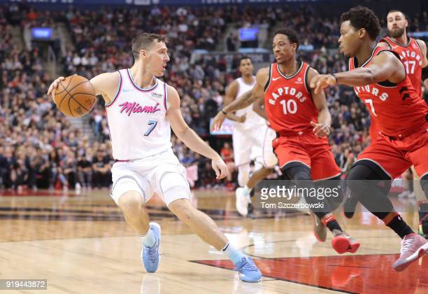 Goran Dragic of the Miami Heat dribbles as Kyle Lowry of the Toronto Raptors and DeMar DeRozan defend against him at Air Canada Centre on February 13...