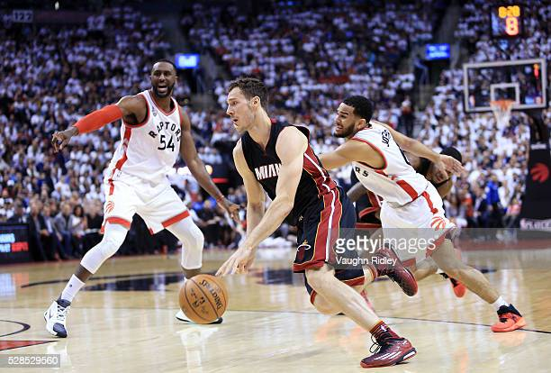 Goran Dragic of the Miami Heat dribbles the ball as Patrick Patterson and Cory Joseph of the Toronto Raptors defend in the second half of Game Two of...