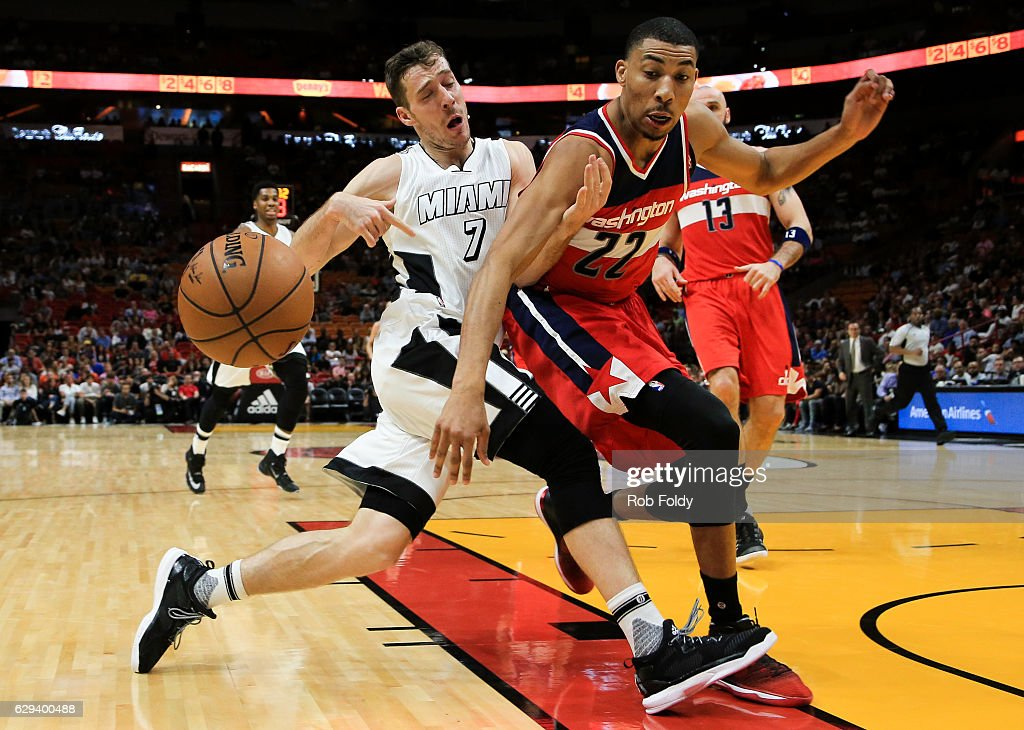 Goran Dragic #7 of the Miami Heat has the ball knocked loose by Otto Porter Jr. #22 of the Washington Wizards during the first half of the game at American Airlines Arena on December 12, 2016 in Miami, Florida.