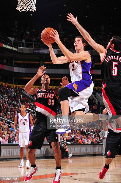 Goran Dragic of the Phoenix Suns drives for a shot between Dante Cunningham and Rudy Fernandez of the Portland Trail Blazers in an NBA game played on...