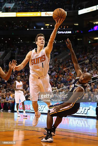 Goran Dragic of the Phoenix Suns is called for charging as he attempts a shot over John Lucas III of the Utah Jazz during the first half of the NBA...