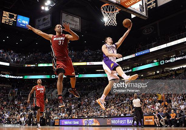 Goran Dragic of the Phoenix Suns lays up a shot past Shane Battier of the Miami Heat during the NBA game at US Airways Center on November 17 2012 in...