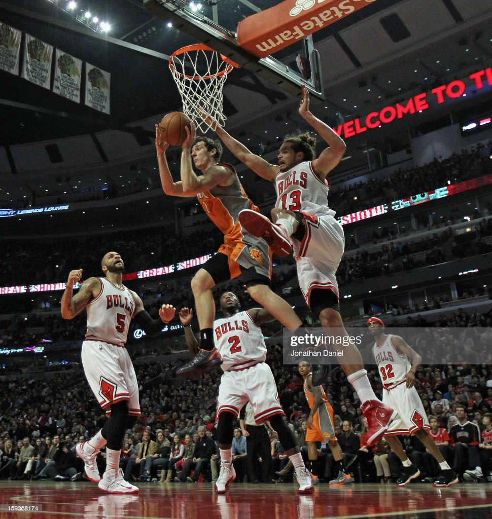 Goran Dragic #1 of the Phoenix Suns leaps to pass over (L-R) Carlos Boozer #5, Nate Robinson #2 and Joakim Noah #13 of the Chicago Bulls at the United Center on January 12, 2013 in Chicago, Illinois.