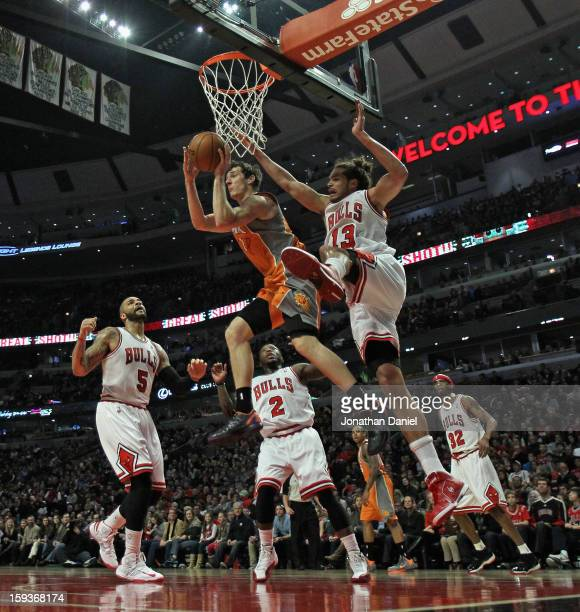 Goran Dragic of the Phoenix Suns leaps to pass over Carlos Boozer Nate Robinson and Joakim Noah of the Chicago Bulls at the United Center on January...