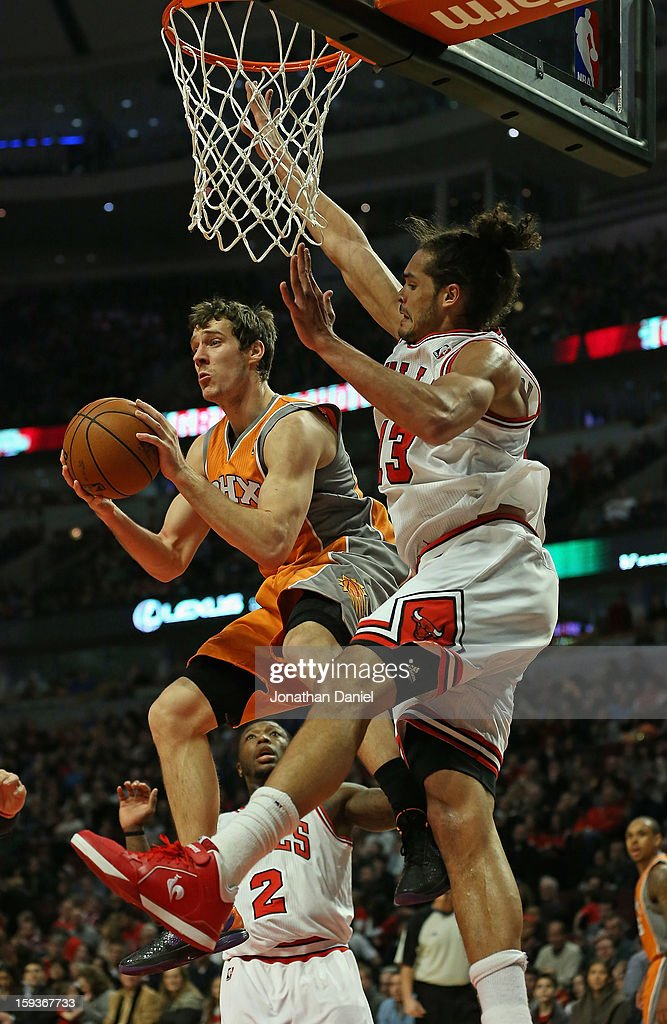 Goran Dragic #1 of the Phoenix Suns puts leaps to pass under pressure from Joakim Noah #13 and Nate Robinson #2 of the Chicago Bulls at the United Center on January 12, 2013 in Chicago, Illinois.
