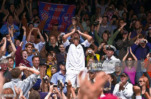 Goran Ivanisevic of Croatia celebrates in the crowd on Centre Court after he beat Pat Rafter of Australia to win the Wimbledon men's singles title on...