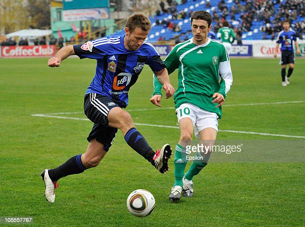 Goran Maznov of FC Tom Tomsk battles for the ball with Andrei Karyaka of FC Saturn during the Russian Football League Championship match between FC...