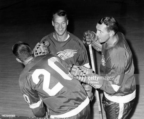 Gordie Howe and Bill Gadsby of the Detroit Red Wings joke around with teammate Don McKenney during practice on September 25 1965 at the Detroit...