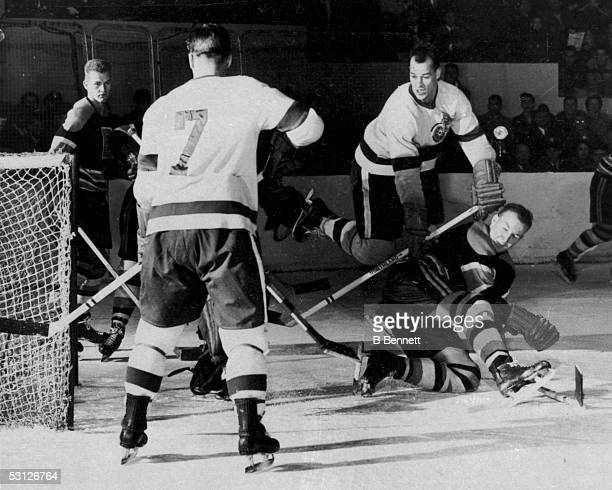 Gordie Howe and Ted Lindsay of the Detroit Red Wings fight for the puck during an NHL game against the Boston Bruins on December 28 1952 at Olympia...