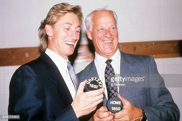 Gordie Howe and Wayne Gretzky of the Los Angeles Kings hold pucks with the number of career points after Gretzky broke Howe's career points record...