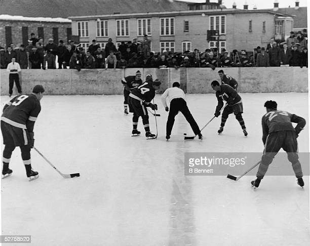 Gordie Howe Dutch Reibel and Ted Lindsay of the Detroit Red Wings line up for the faceoff during an outdoor game against the Marquette Prison Pirates...