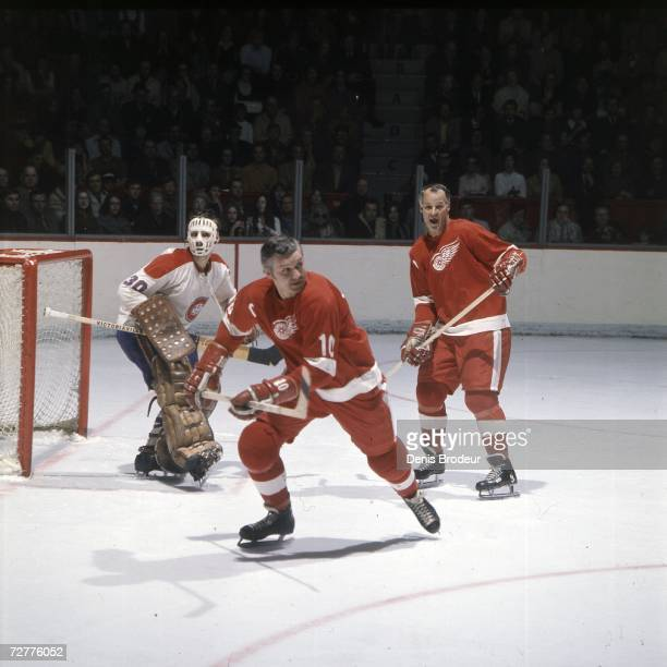 Gordie Howe of the Detroit Red Wings and teammate Alex Delvecchio skate in front of goalie Rogatien Vachon of the Montreal Canadiens during an NHL...