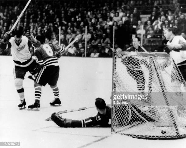 Gordie Howe of the Detroit Red Wings celebrates after he stole the puck and scored on goalie Glenn Hall and Murray Balfour of the Chicago Blackhawks...