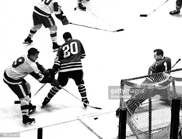 Gordie Howe of the Detroit Red Wings goes for the loose puck as Doug Jarrett and goalie Glenn Hall of the Chicago Blackhawks defend the net on...