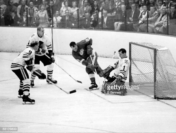 Gordie Howe of the Detroit Red Wings has his shot blocked by goalie Glenn Hall of the Chicago Blackhawks as Bobby Hull and Elmer Moose Vasko of the...