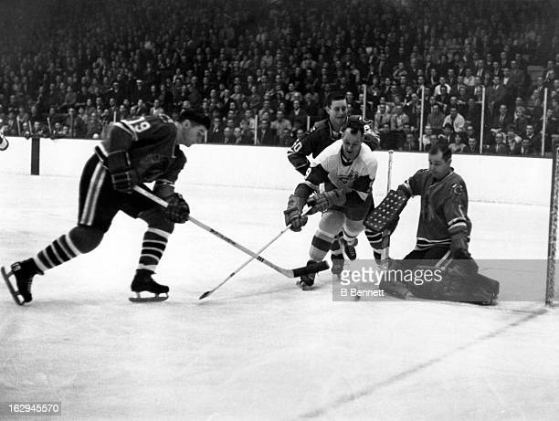 Gordie Howe of the Detroit Red Wings has the puck poke checked away as Al MacNeil Doug Jarrett and goalie Glenn Hall of the Chicago Blackhawks defend...