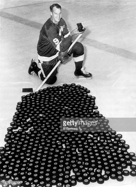 Gordie Howe of the Detroit Red Wings poses with 540 pucks while holding 5 in his hand to show how many more goals he will need to pass Maurice...