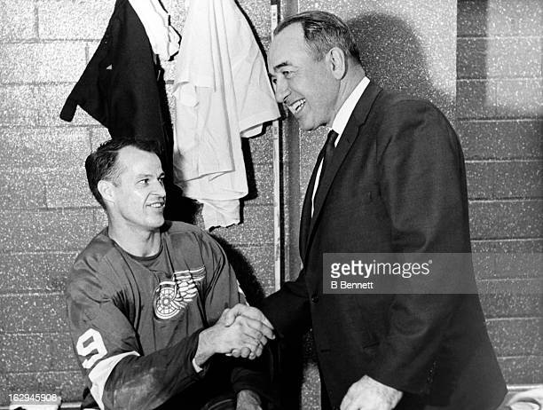 Gordie Howe of the Detroit Red Wings shakes hands with head coach Hector 'Toe' Blake of the Montreal Canadiens after Howe scored the 544th goal of...