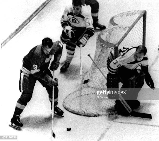 Gordie Howe of the Detroit Red Wings skates with the puck around the net as goalie Gerry Cheevers and Bob Woytowich of the Boston Bruins defend the...