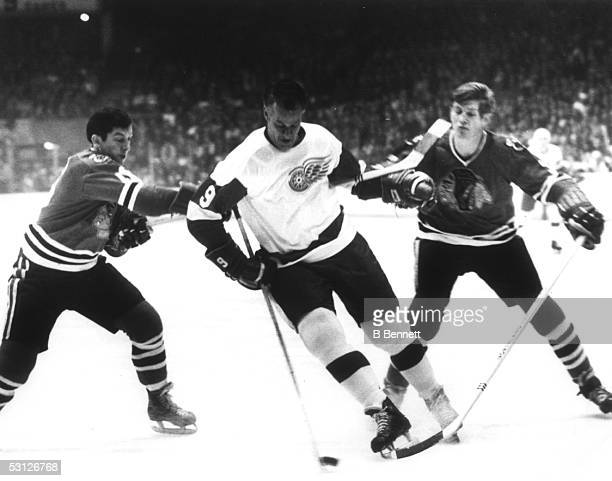 Gordie Howe of the Detroit Red Wings skates with the puck as he battles with Chico Maki and Keith Magnuson of the Chicago Blackhawks during Game 1 of...