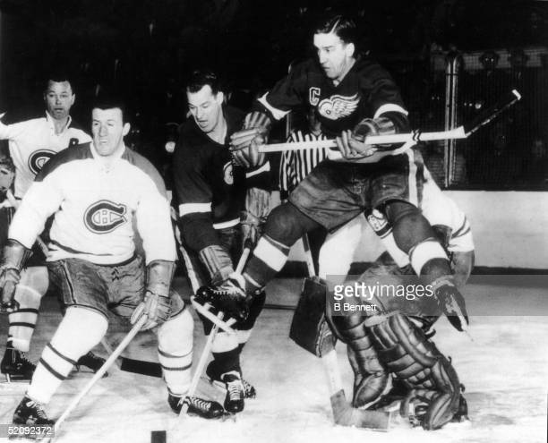 Gordie Howe of the Detroit Red Wings sneaks his stick past Montreal Canadiens Claude Provost while Howe's teammate Ted Lindsay leaps into the air...