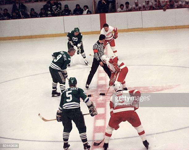 Gordie Howe of the Hartford Whalers faces off against the Detroit Red Wings his former team with his sons Marty and Mark flanking him in a game at...