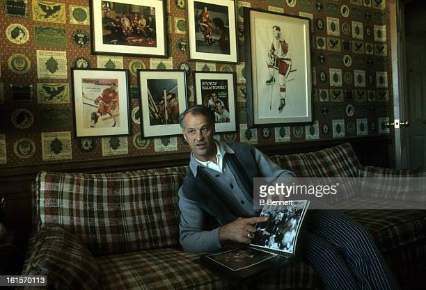 Gordie Howe of the Houston Aeros shows photographs of himself during an interview at his home circa 1975 in Houston Texas