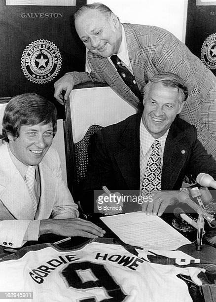 Gordie Howe right is shown with club president Jim Smith and owner Paul Deneau as Howe signs a four year one million dollar contract with the Houston...