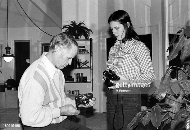 Gordie Howe shows his daughter Cathy a camera at their home circa 1980 in Bloomfield Hills Michigan