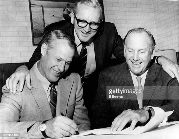 Gordie Howe signs his last 2 year contract with the Detroit Red Wings as general manager Sid Abel and owner Bruce A Norris look on as Howe becomes...