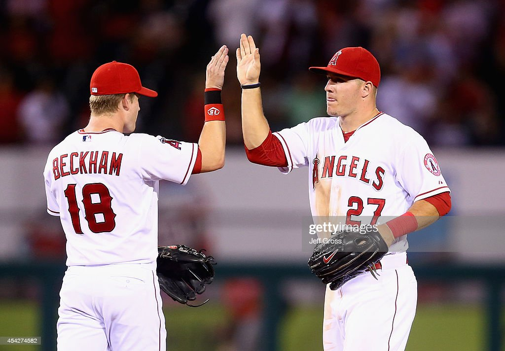 Gordon Beckham #18 and Mike Trout #27 of the Los Angeles Angels of Anaheim celebrate the Angels' 6-1 victory over the Miami Marlins at Angel Stadium of Anaheim on August 27, 2014 in Anaheim, California.