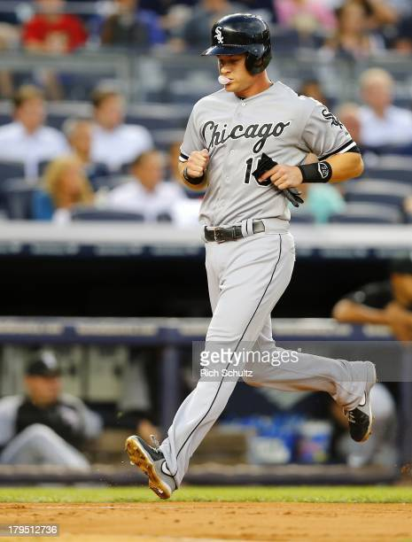 Gordon Beckham of the Chicago White Sox blows a bubble as he scores on a triple by Avisail Garcia in the first inning in a game against the New York...