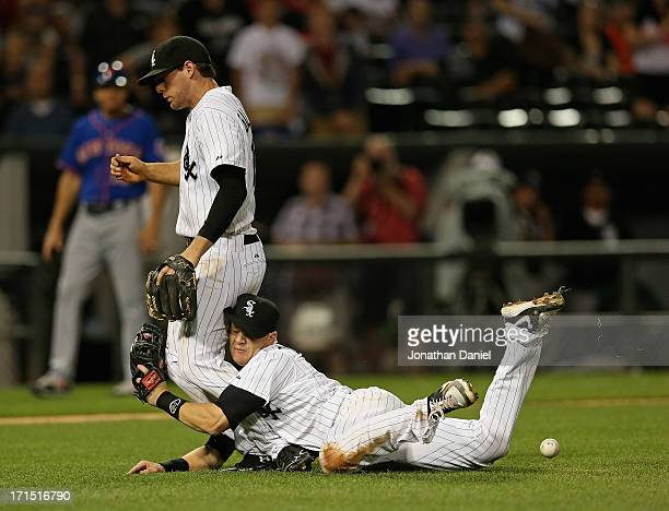 Gordon Beckham of the Chicago White Sox collides with Conor Gillaspie as they try to catch a infield pop fly by Daniel Murphy of the New York Mets in...