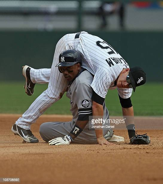 Gordon Beckham of the Chicago White Sox lands on top of Curtis Granderson of the New York Yankees after turning a double play at US Cellular Field on...