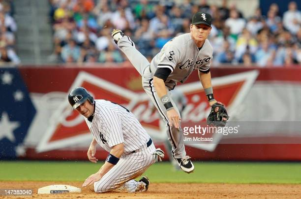 Gordon Beckham of the Chicago White Sox leaps over Chris Stewart of the New York Yankees in an failed attempt to complete a third inning double play...