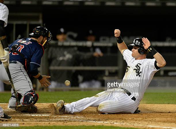 Gordon Beckham of the Chicago White Sox scores past catcher Yan Gomes of the Cleveland Indians on a sacrifice fly hit by Adam Dunn during the eighth...