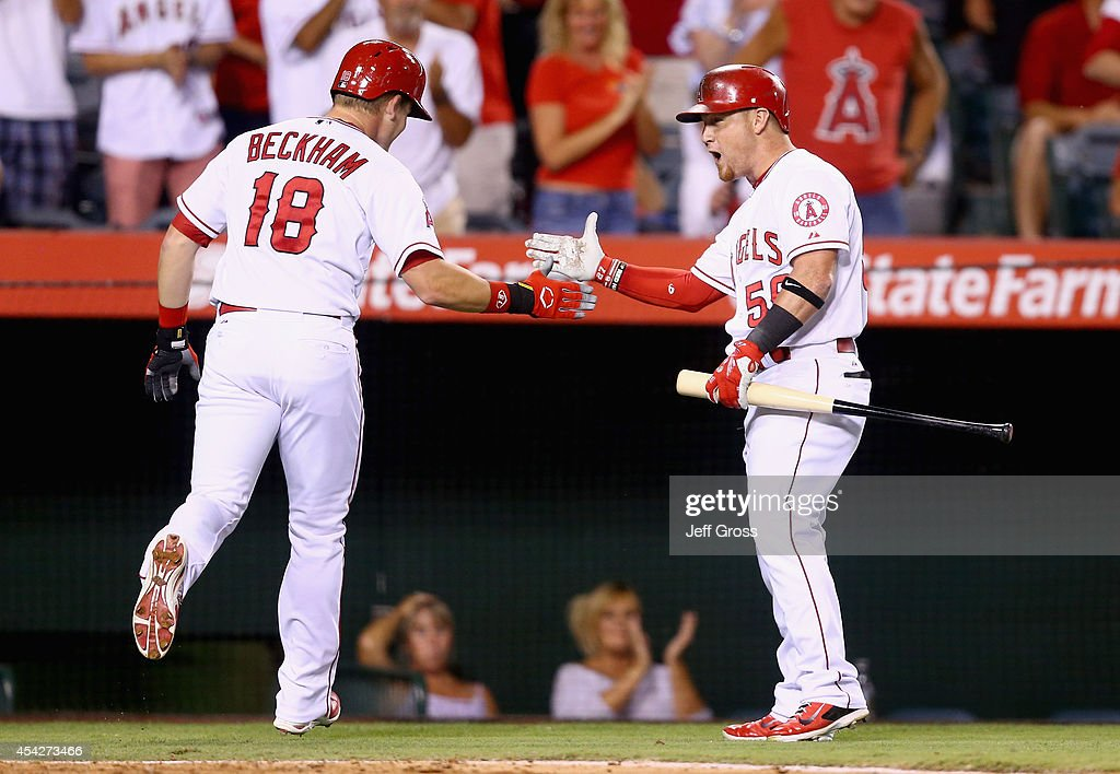 Gordon Beckham #18 of the Los Angeles Angels of Anaheim is congratulated by Kole Calhoun #56 after hitting a solo home run against the Miami Marlins in the fourth inning at Angel Stadium of Anaheim on August 27, 2014 in Anaheim, California.