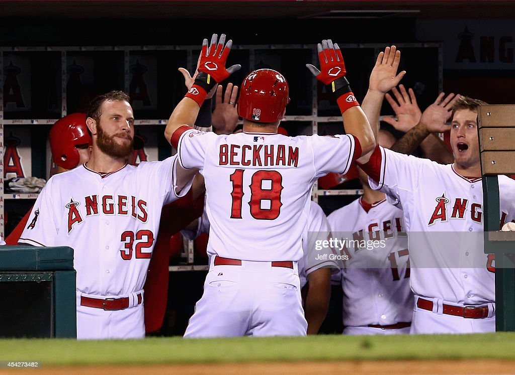 Gordon Beckham #18 of the Los Angeles Angels of Anaheim is congratulated by Josh Hamilton (L) #32 and David Freese (R) #6 after hitting a solo home run against the Miami Marlins in the fourth inning at Angel Stadium of Anaheim on August 27, 2014 in Anaheim, California.
