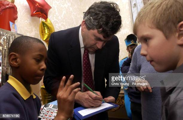 Gordon Brown signs autographs for children at The Chancellor's residence in Downing Street during the his annual Children's Christmas Party