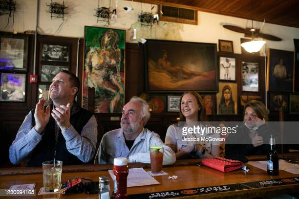 Gordon Burns, Kyle Hannon, Kelly Hannon and Tara Landy watch and cheer during the televised Presidential Inauguration ceremony at Manuel's Tavern on...