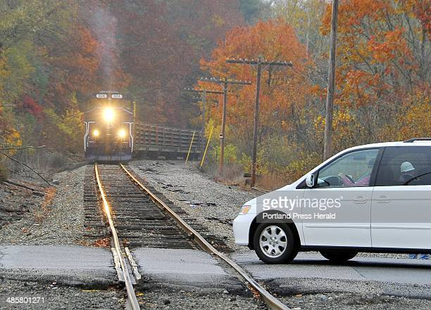 Gordon Chibroski/ Staff Photographer Wednesday October 27 2010 The last car slips through the crossing as the train approaches the Falmouth Road...