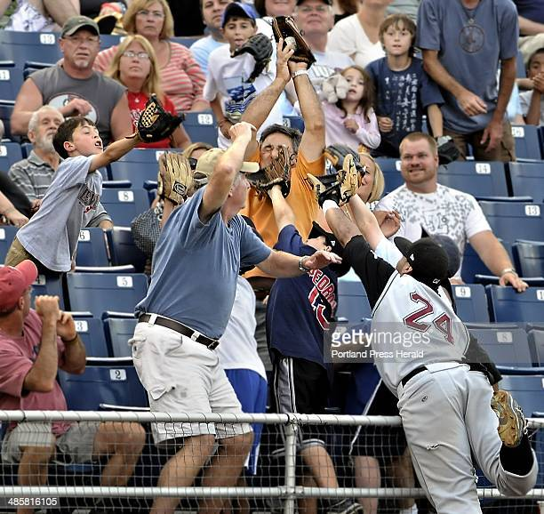 Gordon Chibroski/Staff Photographer Altoona third baseman Pedro Alvarez gets upstaged by a fan who rises above the rest of the wouldbe fielders and...