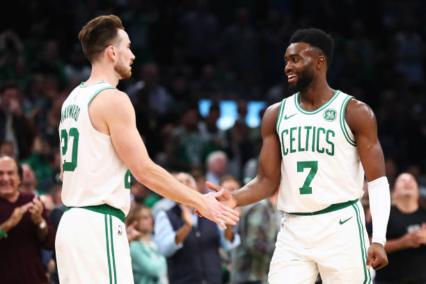 Gordon Hayward high fives Jaylen Brown of the Boston Celtics during a game against ethics's Philadelphia 76ers at TD Garden on October 16 2018 in...