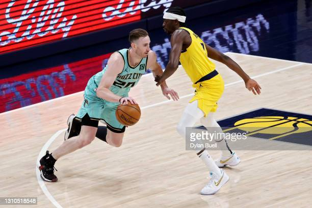 Gordon Hayward of the Charlotte Hornets dribbles the ball while being guarded by Justin Holiday of the Indiana Pacers in the first quarter at Bankers...
