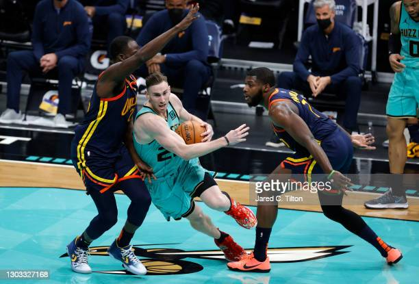 Gordon Hayward of the Charlotte Hornets drives to the basket against Draymond Green and Eric Paschall of the Golden State Warriors during the fourth...