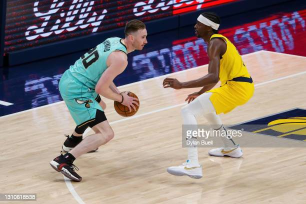 Gordon Hayward of the Charlotte Hornets handles the ball while being guarded by Justin Holiday of the Indiana Pacers in the first quarter at Bankers...