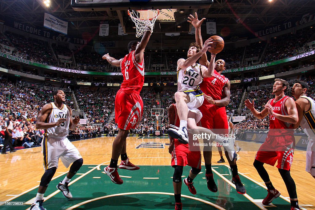 Gordon Hayward #20 of the Utah Jazz attempts a layup against Terrence Jones #6 and Greg Smith #4 of the Houston Rockets at Energy Solutions Arena on November 19, 2012 in Salt Lake City, Utah.