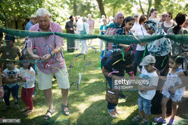 Gordon Leadbeater the father of murdered Member of Parliament Jo Cox joins others in tying a ribbon onto a piece of netting during a 'Great Get...
