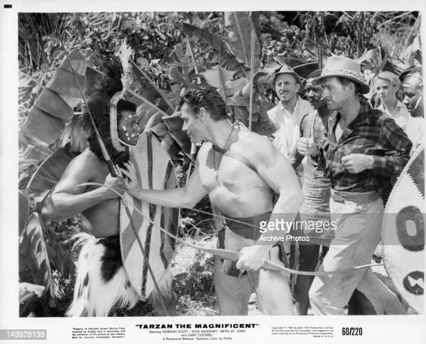 Gordon Scott puts his hand on native with Jock Mahoney right behind him in a scene from the film 'Tarzan The Magnificent', 1960.