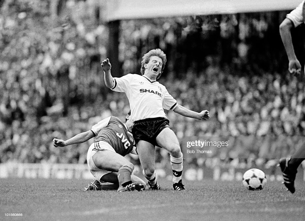 Gordon Strachan of Manchester United (right) falls after a challenge from Stewart Robson of Arsenal during their Division One match held at Highbury, London on 23rd August 1986. Arsenal beat Manchester United 1-0. (Bob Thomas/Getty Images).